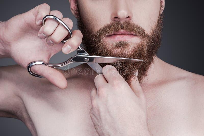 Het snijden van zijn perfecte baard stock afbeeldingen