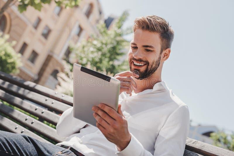 Het sociale leven Jonge het glimlachen mensenzitting op een bank in het park, holding zijn tablet De rust, mededeling en ontspant stock fotografie