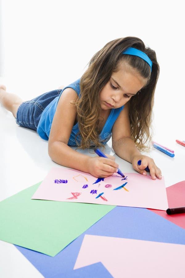Het Spaanse meisje kleuren op vloer. stock fotografie