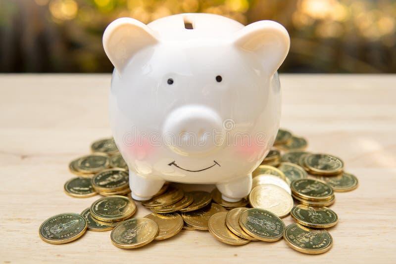 Het spaarvarken en stapelt vele geldmuntstukken op een houten lijst op - Het concept van het besparingsgeld, sparen geld met het  stock afbeeldingen