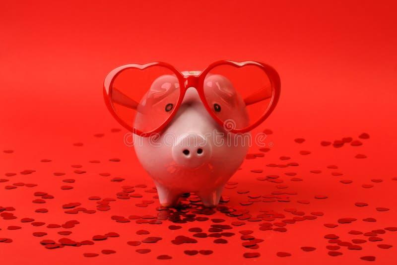 Het spaarvarken in liefde met rode hartzonnebril die zich op rode achtergrond met glanzend rood hart bevinden schittert stock afbeelding