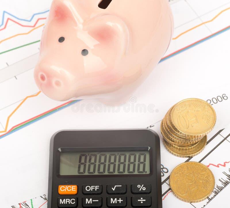 Het spaarvarken met calculator, sluit omhoog mening stock afbeeldingen