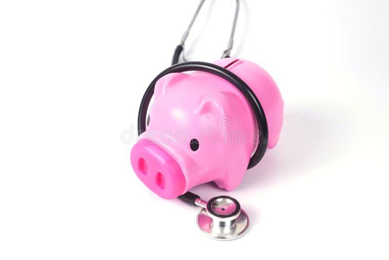 het spaarvarken met stethoscoop bewaart binnen gezondheid stock foto's