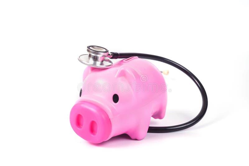 het spaarvarken met stethoscoop bewaart binnen gezondheid royalty-vrije stock foto's