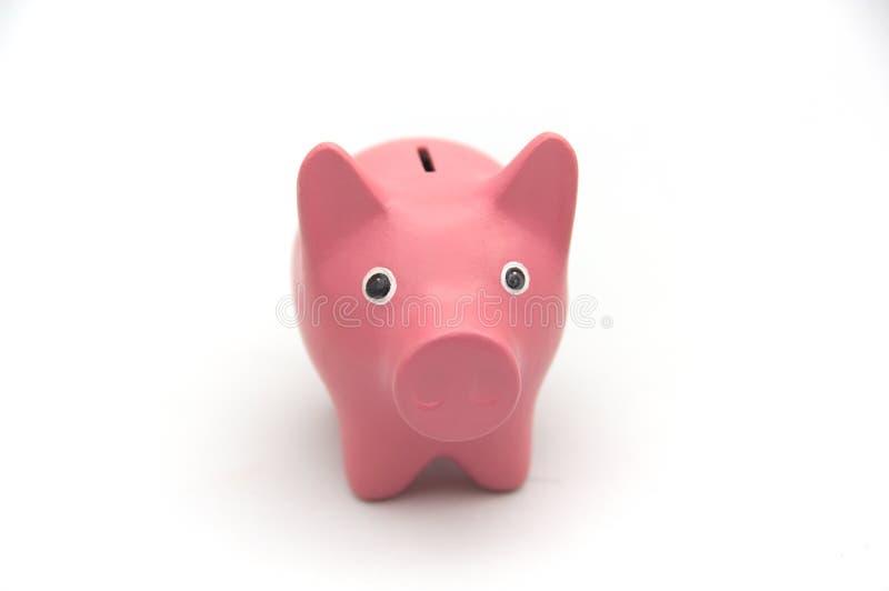 Het spaarvarken in roze kleur op witte achtergrond bekijkt camera stock foto's