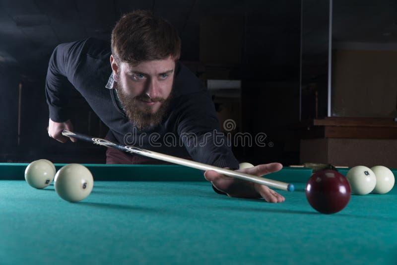 Het speelbiljart van de mens Concentratie in eigen zak steek de bal stock afbeelding