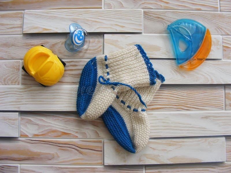 Het speelgoed van de kinderen` s Wereld op een houten achtergrond met baby` s sokjes stock foto's