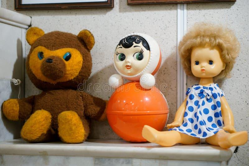 Het speelgoed van oude uitstekende kinderen - een pop, een beer en een tuimelschakelaar op een schoorsteenmantel stock foto