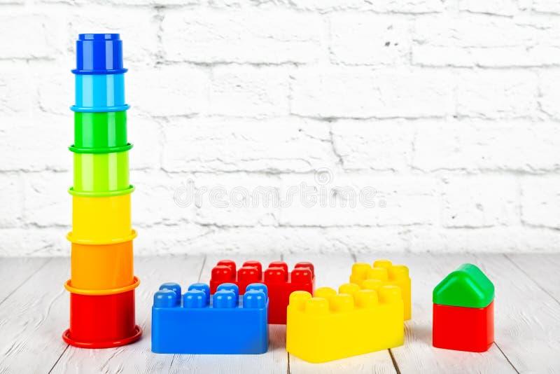 Het speelgoed van plastic kinderen op houten lijst aangaande een bakstenen muurbackgrou stock foto's