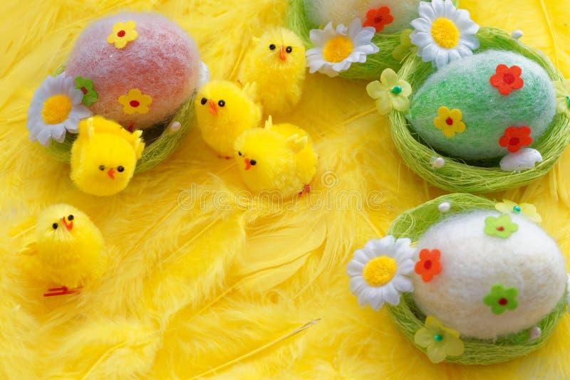 Het speelgoedkuikens en eieren van baby gele Pasen op een achtergrond van veren Feestelijke groetkaart royalty-vrije stock foto