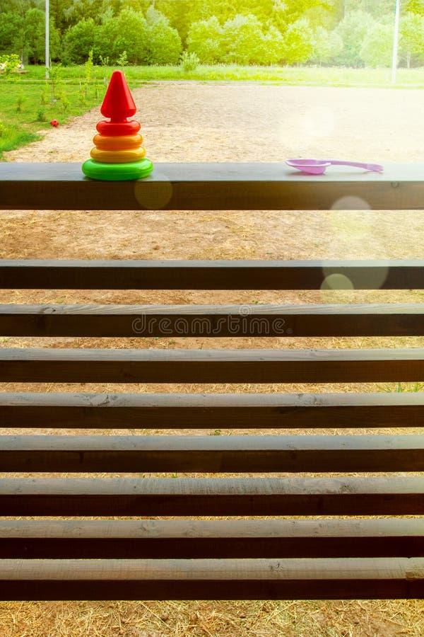 Het speelgoedpiramide van kinderen en plastic lilac troffel op het traliewerk op het zonovergoten terras van een buitenhuis verti stock foto's
