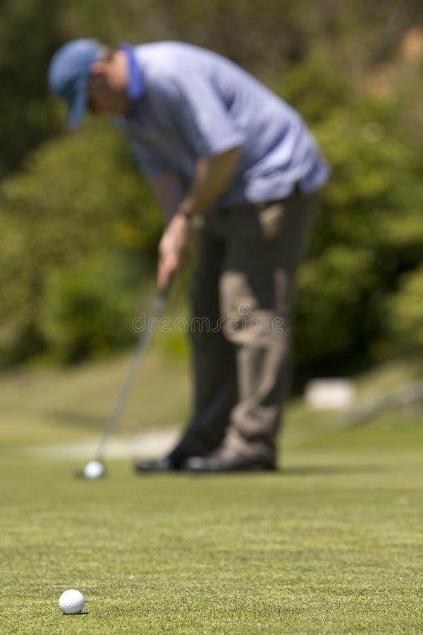 Het speelgolf van de mens op een verse groene golfcursus royalty-vrije stock foto