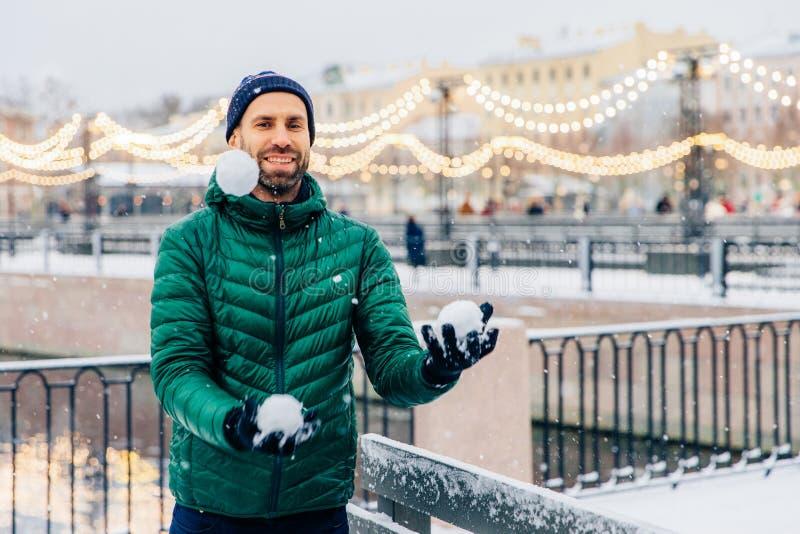 Het speelse glimlachende mannetje jongleert met met sneeuwballen werpt hen in lucht, stock foto's