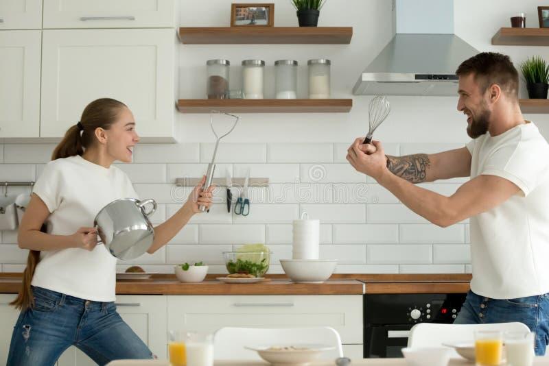 Het speelse jonge paar spelen met keukengerei in keuken stock foto