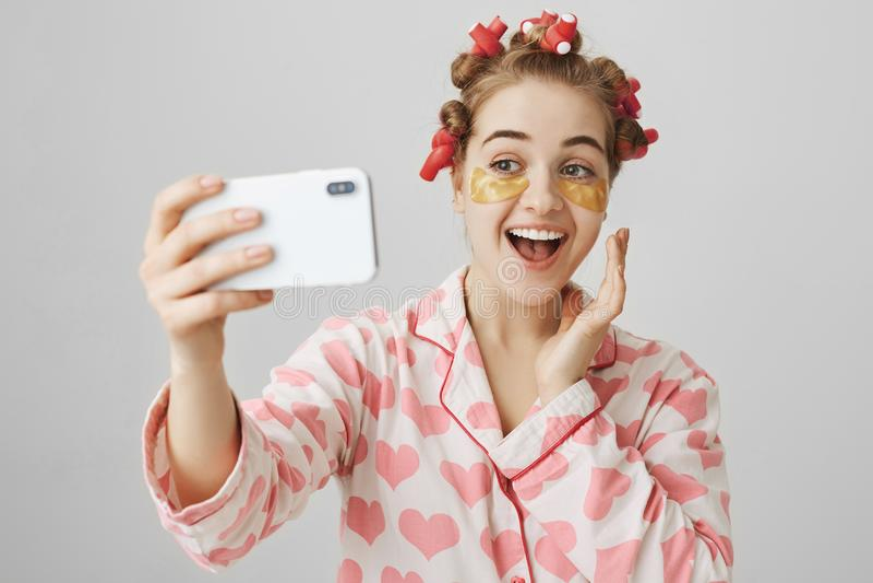 Het speelse knappe meisje die thuis schoonheidsprocedures maken, die haar-krulspelden, nachthemden en oog dragen herstelt masker, stock foto