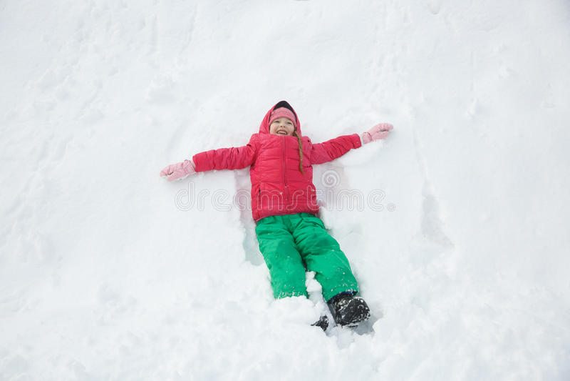 Het speelse meisje spelen in sneeuw, die een sneeuwengel maken royalty-vrije stock afbeelding