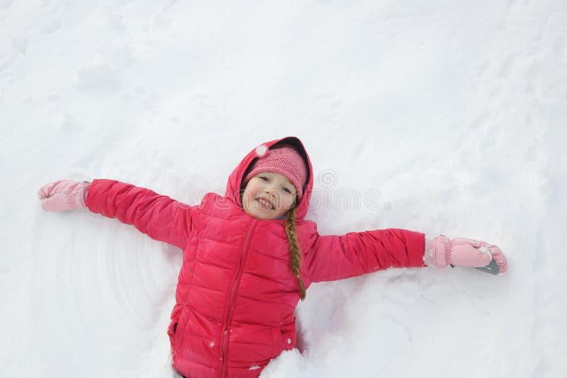 Het speelse meisje spelen in sneeuw, die een sneeuwengel maken royalty-vrije stock foto