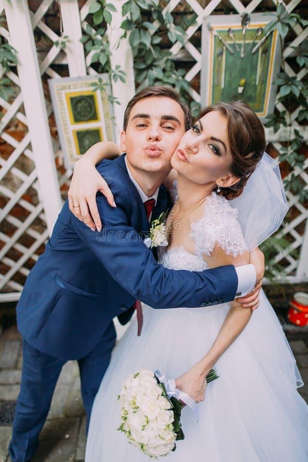 Het speelse mooie bruid en bruidegom stellen in openlucht bij hun huwelijksdag Close-up royalty-vrije stock foto's