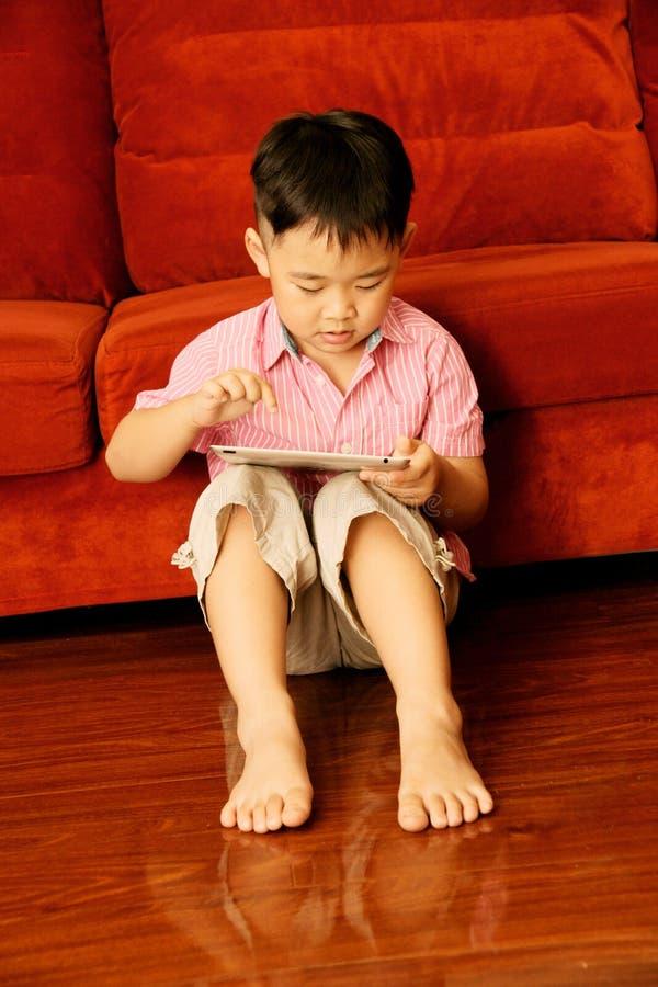 Het speelspel van de jongen op tablet aandachtig stock foto