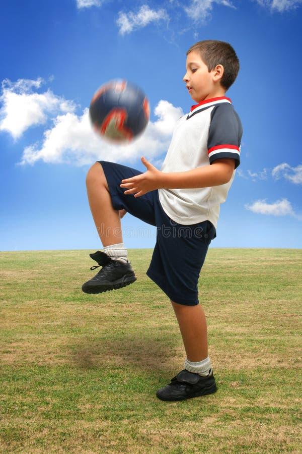 Het speelvoetbal van het jonge geitje buiten royalty-vrije stock afbeeldingen