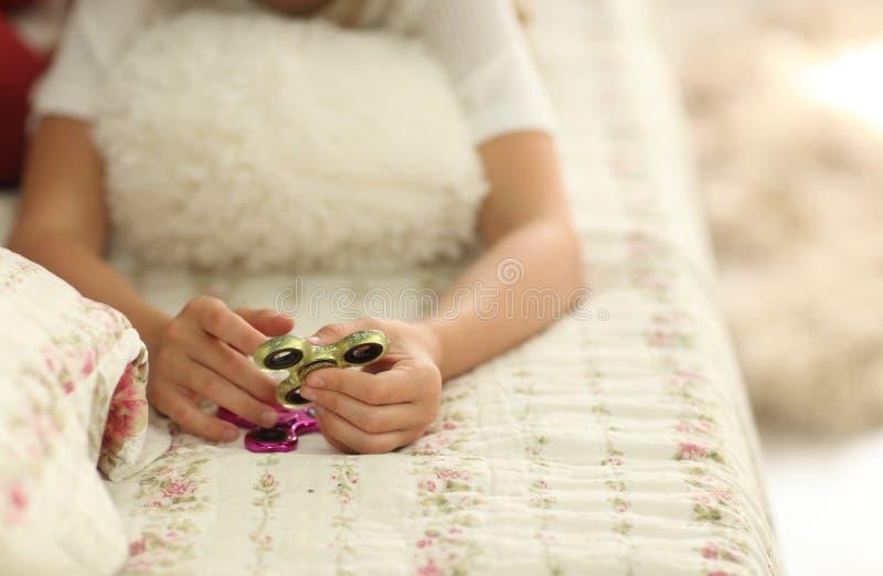 Het spel met friemelt spinner De meisjesspelen met Fidget Spinners thuis op bed, het concept het verlichten van spanning, ontwikk stock fotografie