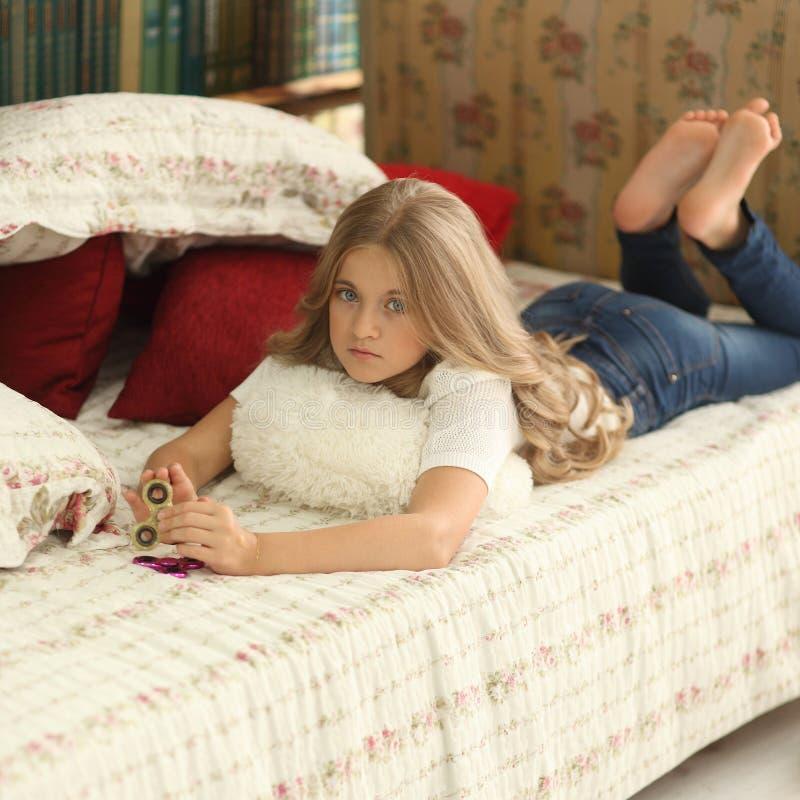 Het spel met friemelt spinner Meisjesspelen met Fidget Spinners thuis op bed stock fotografie