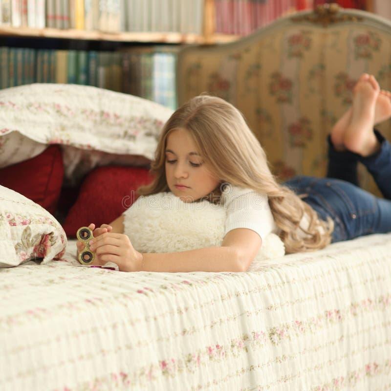 Het spel met friemelt spinner Meisjesspelen met Fidget Spinners thuis op bed royalty-vrije stock afbeelding