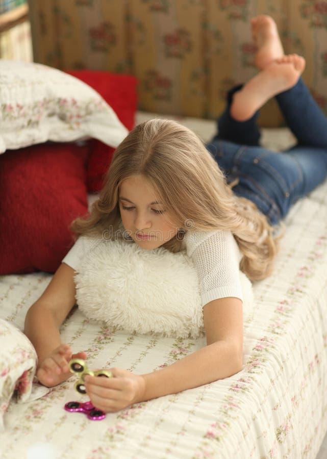 Het spel met friemelt spinner Meisjesspelen met Fidget Spinners thuis op bed, het concept het verlichten van spanning stock fotografie