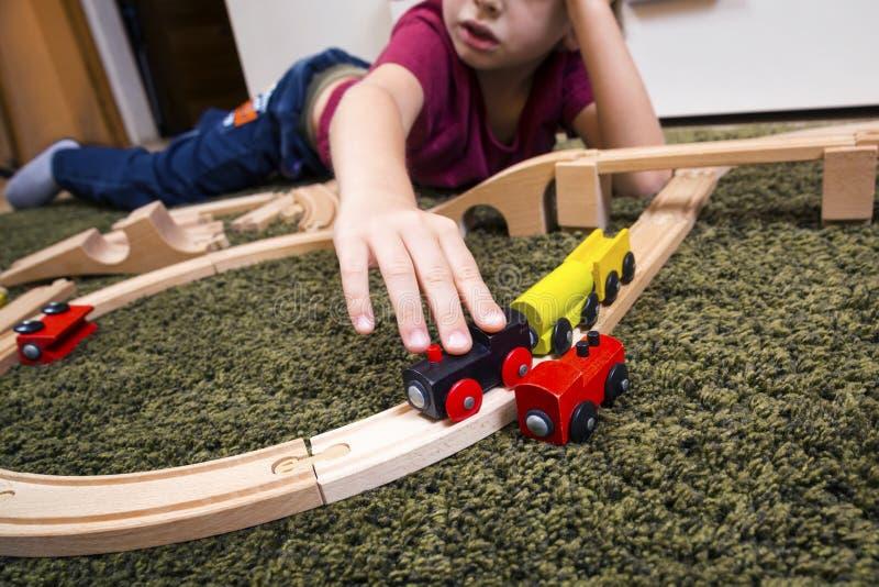 Het spel van de kindjongen met houten trein, bouwt stuk speelgoed thuis spoorweg of stock foto
