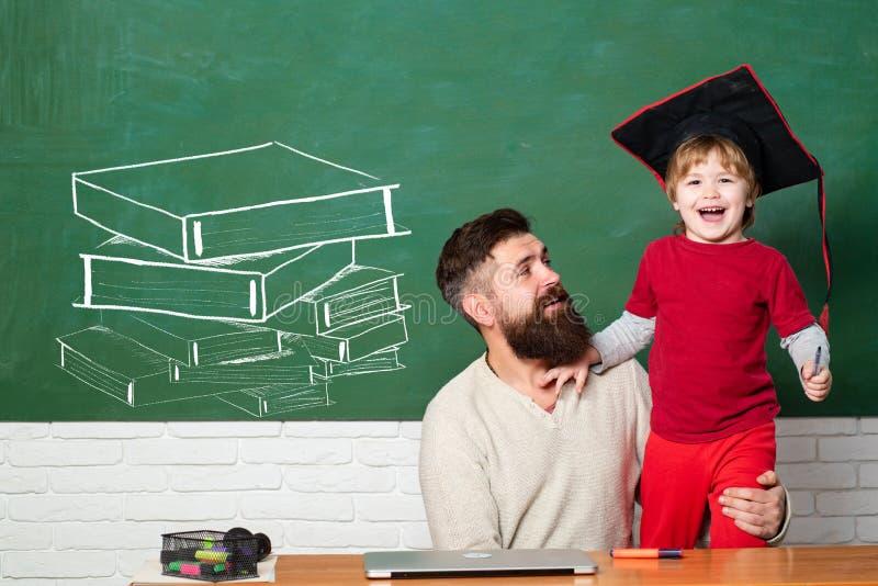Het spel van de mensenleraar met kleuterkind Zijnd blij en opgewonden Terug naar school en onderwijsconcept Bord stock foto