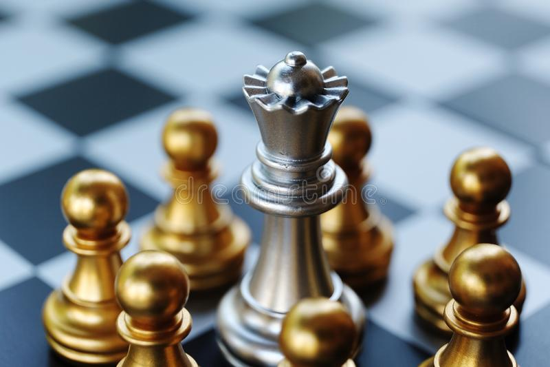 Het Spel van de schaakraad Koningintribune en omringd door enemy' s panden Het verwijzen naar degenen die in een probleem is stock fotografie