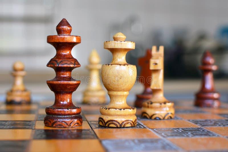 Het spel van de schaakraad met nadruk op houten 'zwarte 'koninginstukken stock afbeeldingen