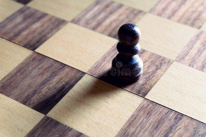 Het Spel van de schaakraad Zwarte pandtribune opmerkelijk onder zacht licht Het schaak stelt bischoppen voor Gelukkige zakenman d royalty-vrije stock afbeelding