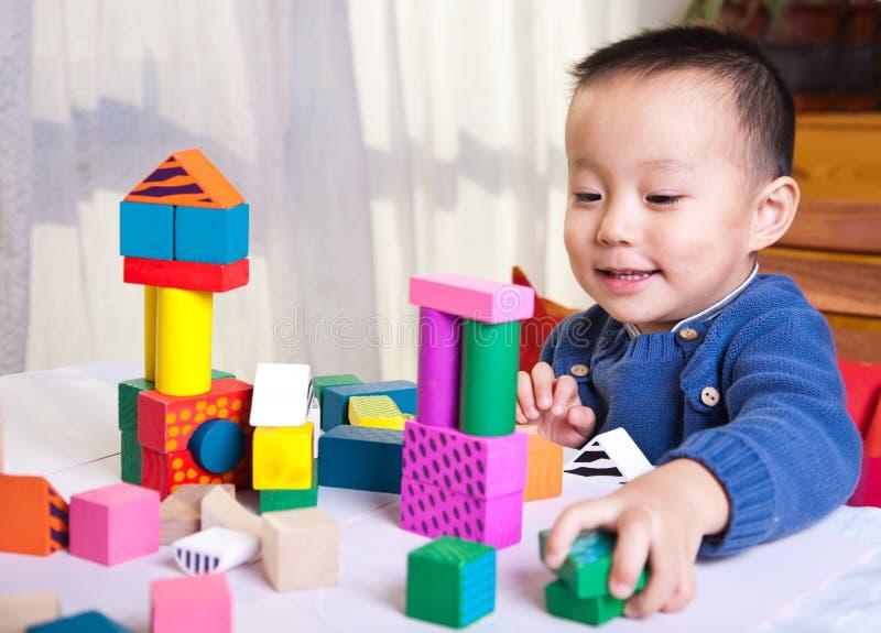 Het spel van het kind met houten blokken stock afbeeldingen