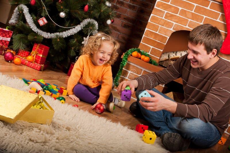 Het spel van het meisje met papa dichtbij Kerstboom stock foto