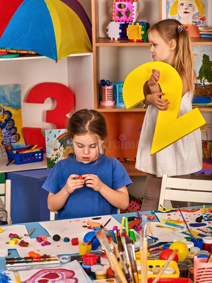 Het spel van het kinddeeg in school Plasticine voor kinderen stock afbeeldingen