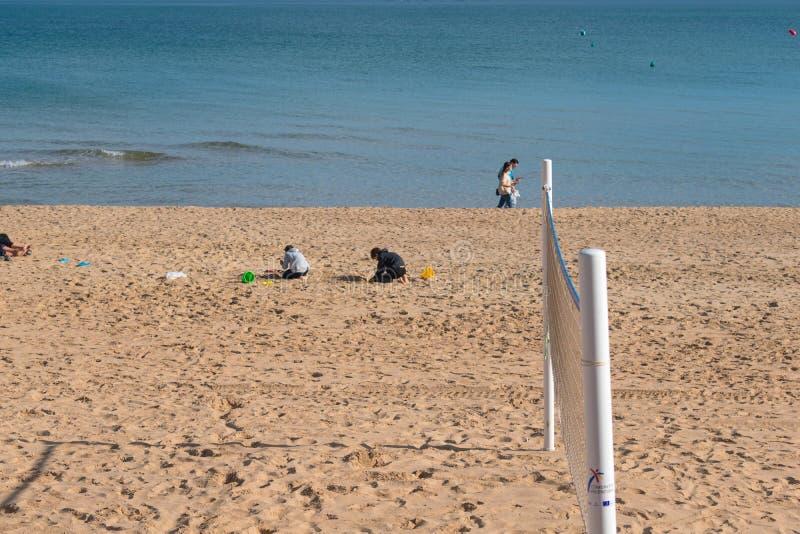 Het spel van kinderen in zand van het strand dichtbij van overzees royalty-vrije stock foto