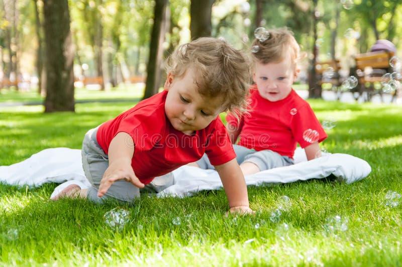 Het spel van kinderentweelingen op het gras royalty-vrije stock foto's