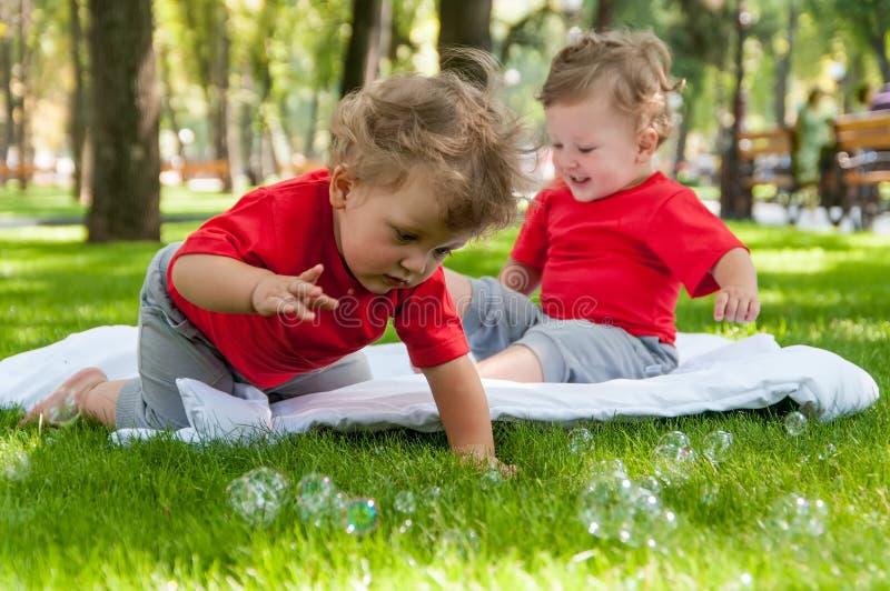 Het spel van kinderentweelingen op het gras royalty-vrije stock afbeeldingen