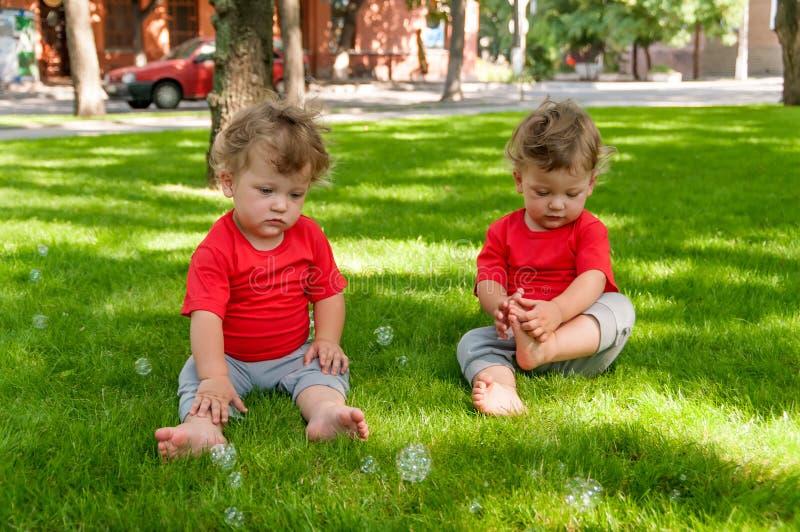 Het spel van kinderentweelingen op het gras met zeepbels royalty-vrije stock foto