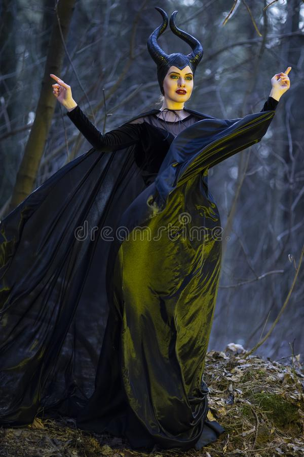 Het Spel van het kostuumdrama Geheimzinnige en Magische Maleficent Vrouw met Hoornen die in de Lente Leeg Bos met Golvende Sjaal  royalty-vrije stock fotografie