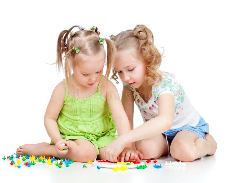 Het spel van twee jonge geitjeszusters samen stock afbeeldingen