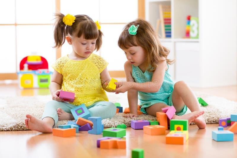 Het spel van twee vriendenjonge geitjes samen in kleuterschool, opvang of huis royalty-vrije stock fotografie