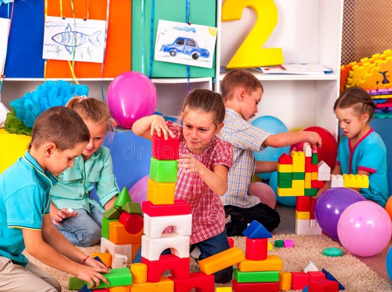 Het spelblokken van groepskinderen op vloer stock fotografie