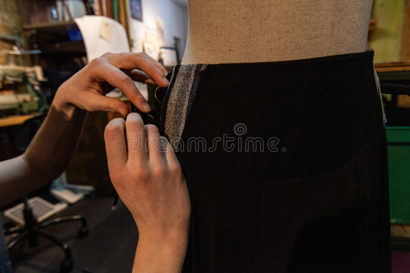 Het spelden van zwarte kleding op een mannequin stock afbeelding