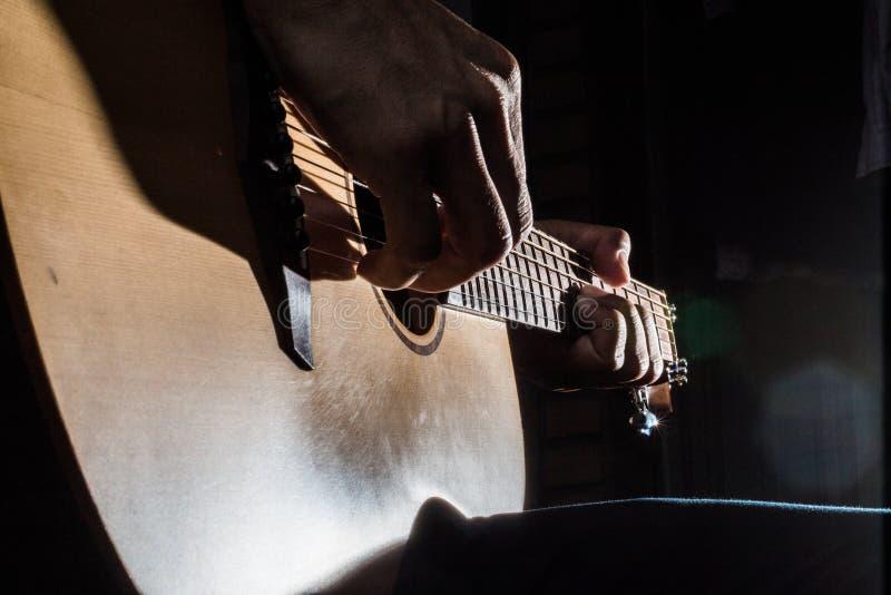 Het spelen akoestische gitaar op rustige verlichtingsachtergrond stock afbeelding