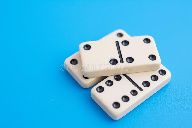 Het spelen domino's op een blauw stock afbeelding