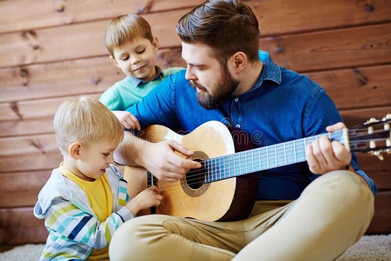 Het spelen gitaar met vader stock fotografie