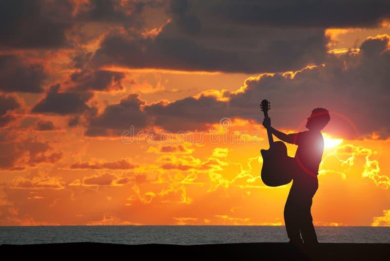 Het spelen gitaar op het strand bij zonsondergang stock foto's