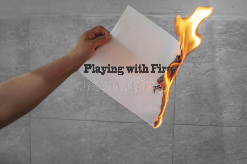 Het spelen met de tekst van brandwoorden op brand met het branden van document stock afbeelding